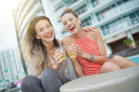 Two attractive funloving friends partying with drinks on rooftop bar in city Stok Fotoğraf