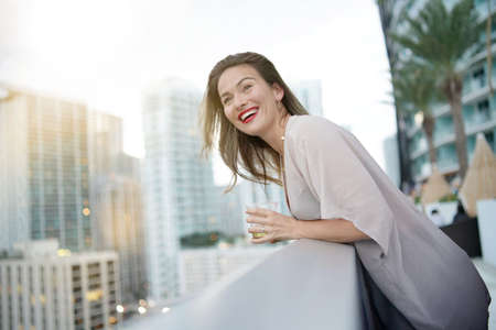 Atttractive elegant young woman having fun smiling on rooftop bar in city Stock Photo