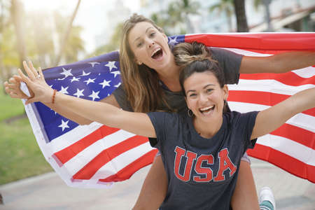 Two dynamic young friends proudly flying the American flag together outdoors Imagens