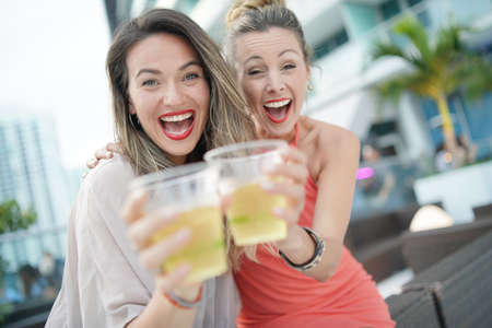 Two attractive funloving friends partying with drinks on rooftop bar in city 免版税图像