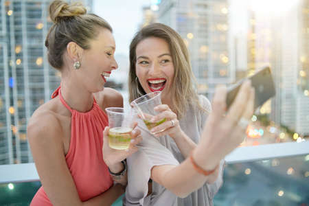 Two beautiful friends taking selfie on rooftop bar with city lights backdrop