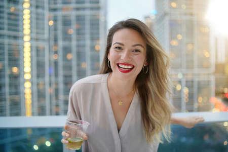 Atractiva mujer joven elegante sonriendo a la cámara en el bar de la azotea en la ciudad