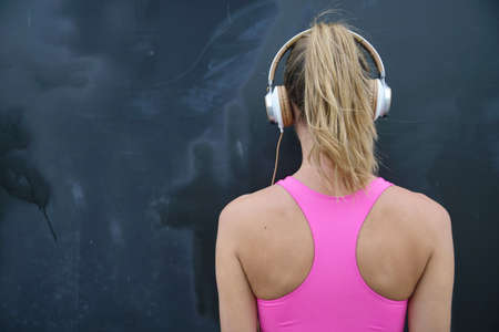 Back of strong toned woman in sportswear and headphones on black background Stock Photo
