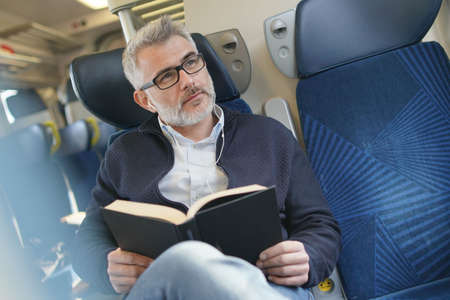 Mature man traveling by train, reading book 免版税图像