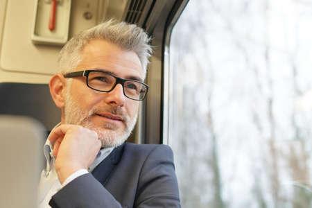 Businessman sitting on a train, looking by window 写真素材