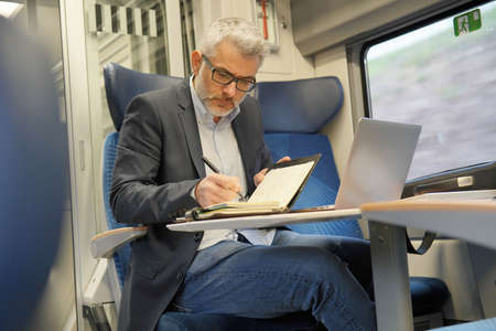 Mature businessman working on laptop while traveling in train Imagens
