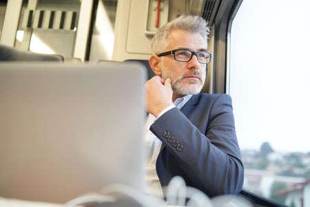 Businessman sitting in train, looking by window 写真素材
