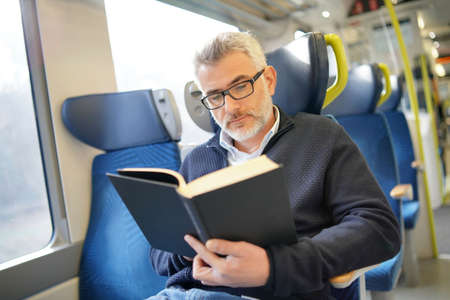 Mature man reading book while traveling on a train 写真素材