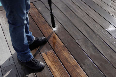 Man using high pressure washer cleaning deck