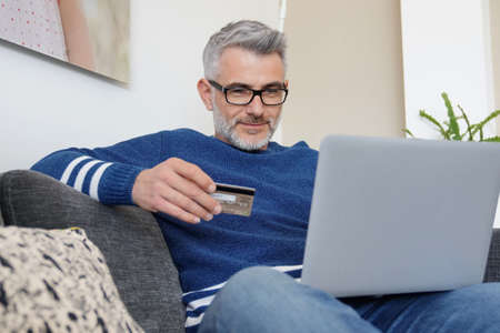 Relaxed man online shopping at home 版權商用圖片