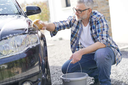 Mature man washing his car with soapy sponge in driveway