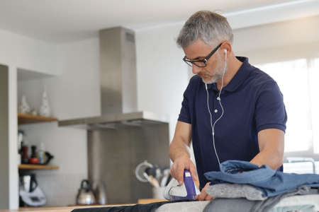 Mature man ironing clean laundry at home