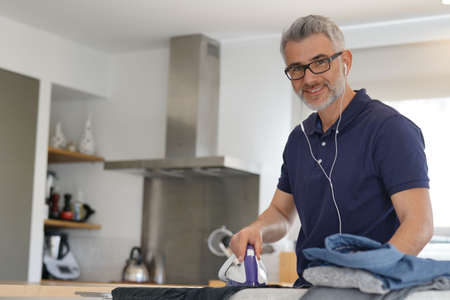 Man looking at camera ironing clothes in modern kitchen