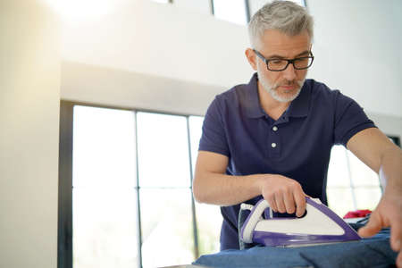 Man ironing shirt in stunnig modern home