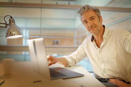 Mature businessman looking at camera at desk