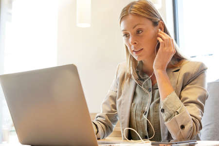 Young professional working with headphones and computer Stock Photo - 119266390