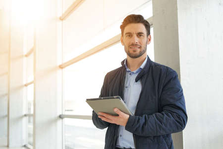 Casual businessman with tablet in contemporary office hallway