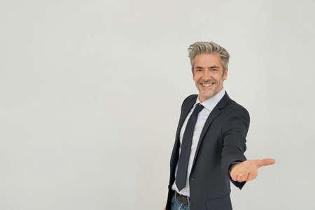 Bello uomo d'affari maturo in piedi su sfondo grigio