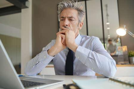 Bell'uomo d'affari in ufficio che contempla