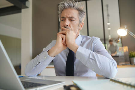Gut aussehender Geschäftsmann im Büro nachsinnen