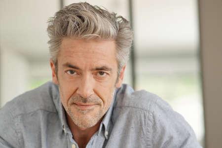 Portret van een knappe volwassen man die naar de camera kijkt in een modern huis
