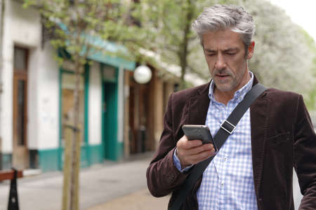 Mature man on cellphone in city centre