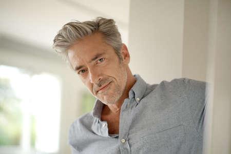 Porträt eines gutaussehenden reifen Mannes, der die Kamera in einem zeitgenössischen Haus betrachtet Standard-Bild
