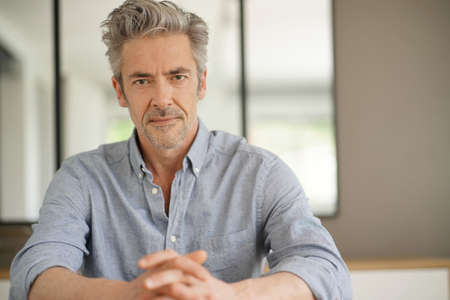 Portrait of handsome mature man looking at camera in contemporary home 스톡 콘텐츠