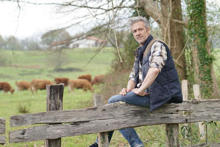 Attractive farmer leaning on fence looking at camera