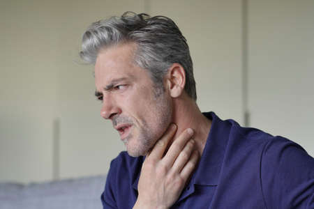 Mature man with sore throat at home