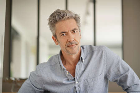Portrait of handsome mature man looking at camera in contemporary home Stok Fotoğraf