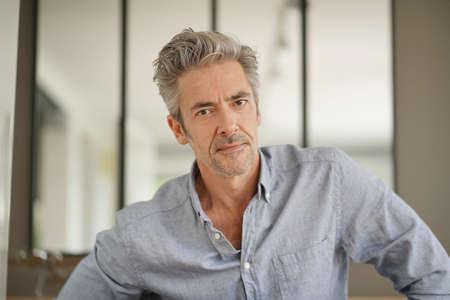 Retrato de hombre maduro guapo mirando a la cámara en casa contemporánea