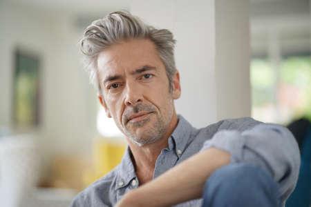 Portrait d'un bel homme mûr regardant la caméra dans une maison contemporaine Banque d'images