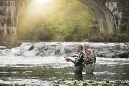 Fly fishing expert guiding novice in river