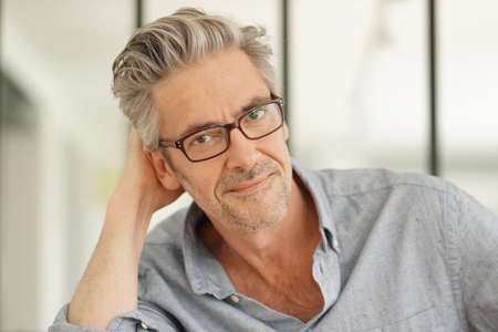 Portrait of handsome mature man wearing glasses smiling at camera 写真素材