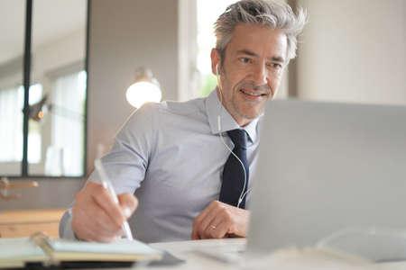 Uomo d'affari in videochiamata in un ufficio contemporaneo