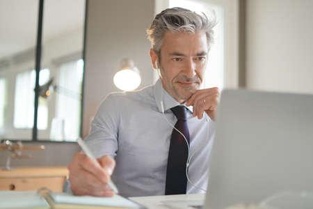 Homme d'affaires sur appel vidéo dans un bureau contemporain