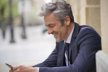 Happy businessman on cellphone taking a break outdoors