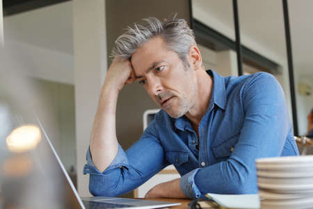 Mature man working from home looking stressed