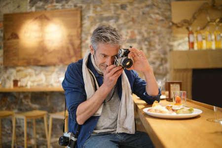 Photographe mature prenant des photos de l'assiette de tapas dans un restaurant espagnol