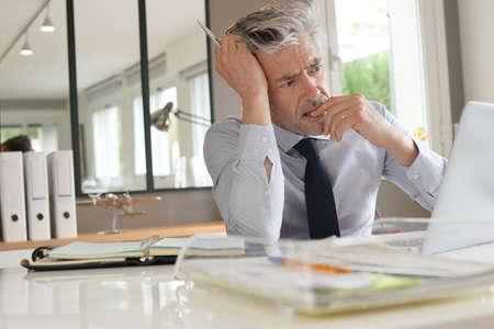 Gestresste zakenman die in een modern kantoor werkt