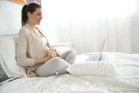 Pregnant woman making video distant call Stockfoto