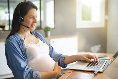 Pregnant woman working from home with laptop and headset Stockfoto
