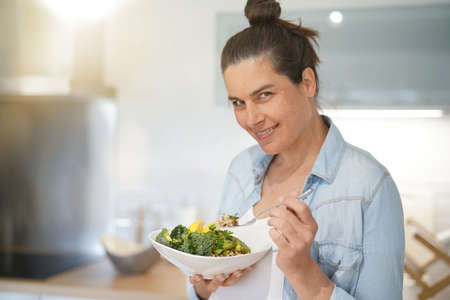 Pregnant woman in home kitchen eating healthy salad