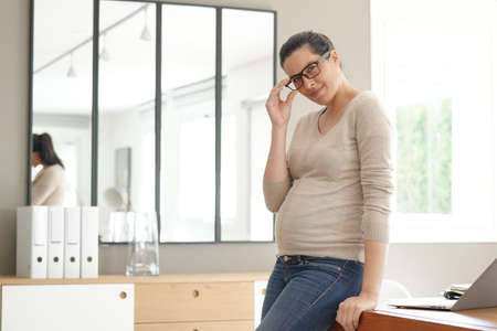 Pregnant businesswoman standing in office