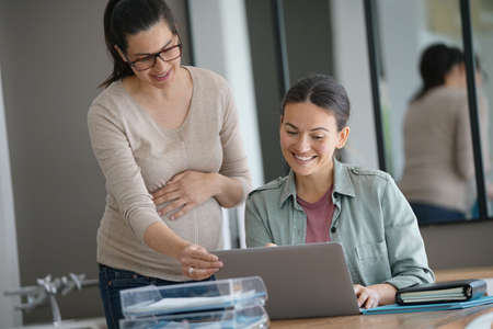 Women working in office on laptop computer