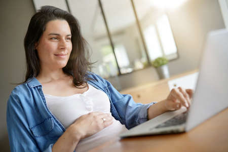 Pregnant woman working from home with laptop
