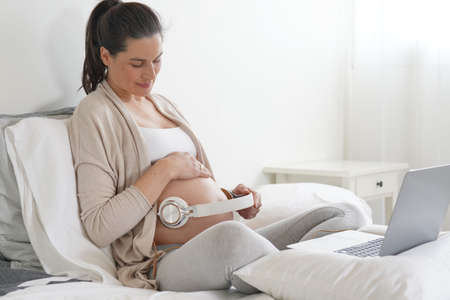 Pregnant woman having her baby listening to music through headphones