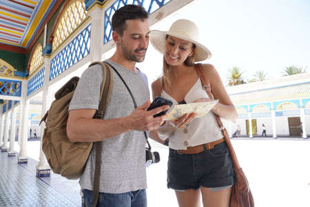 Couple of tourists in La Bahia Palace of Marrakech, reading map