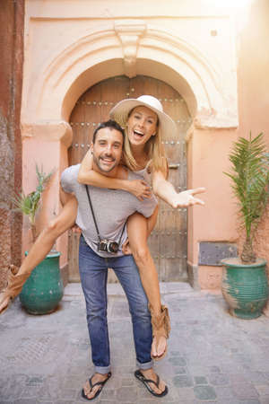 Man giving piggyback ride to girlfriend in street of Marrakech Stockfoto